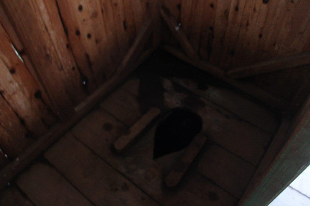 A blurry shot looking inside of the outhouse